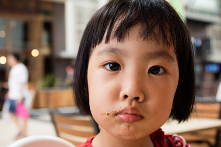 eat smeared: Asian Little Chinese Girl Making a Mess with Food in Outdoor Cafe Stock Photo