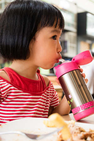 Asian Little Chinese Girl Drinking Water from Stainless Steel Bottle in Outdoor Cafe Stock Photo