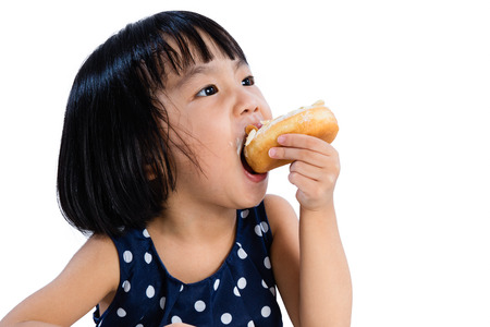 fried food: Asian Little Chinese Girl Eating Donuts in isolated White Background
