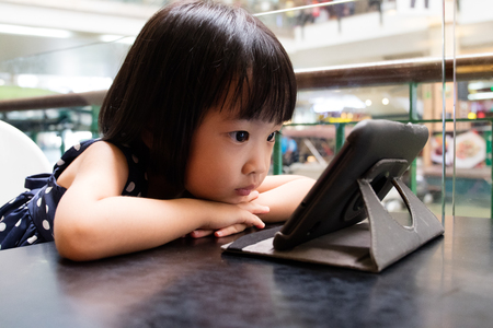 Asian Little Chinese Girl Looking at Digital Tablet in Outdoor Cafe