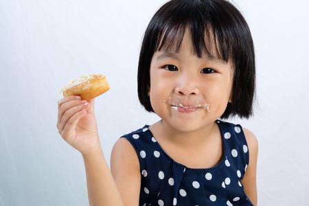 comiendo pan: Pequeña muchacha asiática china que come los anillos de espuma en el fondo blanco aislado Foto de archivo