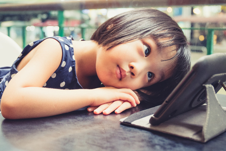 digital device: Asian Little Chinese Girl Looking at Digital Tablet in Outdoor Cafe Stock Photo