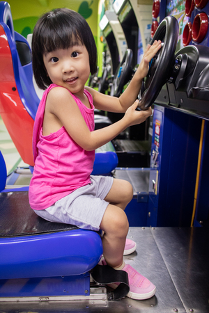 ARCADE GAMES: Asian Little Chinese Girl Playing Arcade Game Machine at a indoor Amusement Playground