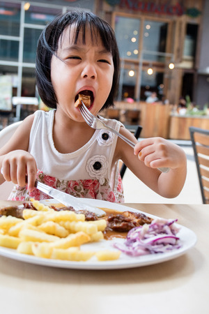 western food: Asian Little Chinese Girl Eating Western Food in Outdoor Cafe