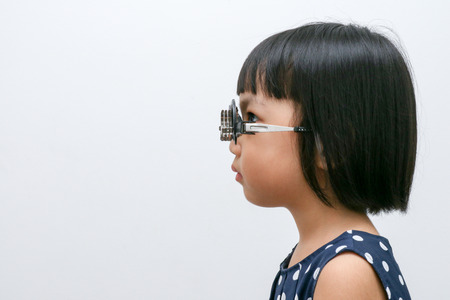 Asian kleine chinesische Mädchen, das Augenuntersuchung in isolierten weißen Hintergrund Standard-Bild