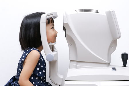 Asian kleine chinesische Mädchen, das Augenuntersuchung durch Auto Refraktometer in isolierten weißen Hintergrund Standard-Bild