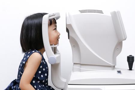examen de la vista: Poco Muchacha china asiática que hace la examinación ojos a través de Refraktometer de automóviles en el fondo blanco aislado Foto de archivo