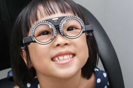 myopia: Asian Little Chinese Girl Doing Eyes Examination at An Optical Shop
