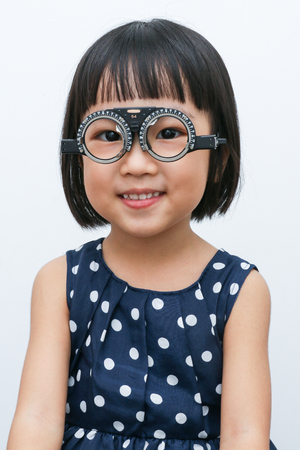 myopia: Asian Little Chinese Girl Doing Eyes Examination in isolated White Background