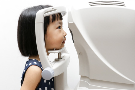 Asian Little Chinese Girl Doing Eyes Examination Through Auto refraktometer in isolated White Background 스톡 콘텐츠