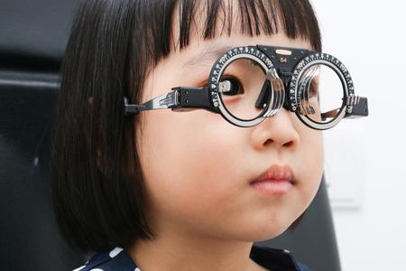 アジア小さな中国の少女やって目試験分離ホワイト バック グラウンドで 写真素材