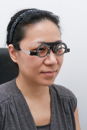 optical equipment: Asian Woman Doing Eyes Examination at Optics Store