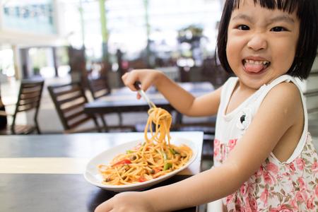 屋外カフェでアジア小さな中国の少女食べるスパゲッティ