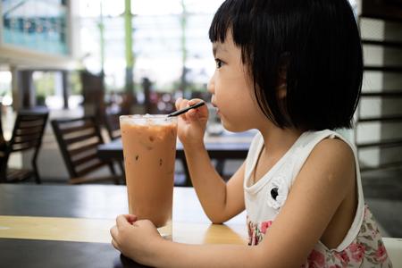 アジアの中国の女の子が屋外カフェでアイス ミルク ティーを飲んで