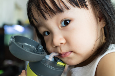 Asian Little Chinese Girl Drinking Water at Home