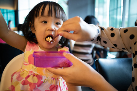 mouthful: Asian Mother Feeding Kid Daughter Food in a Restaurant Stock Photo