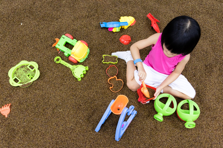 Asian Chinese Little Girl Playing with sand at indoor playground Stock Photo