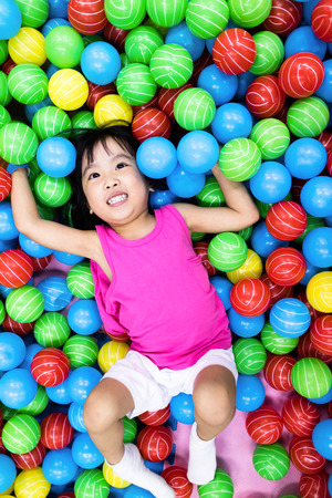 playcentre: Asian Little Chinese Girl Playing with Colorful Plastic Balls in Indoor Playground