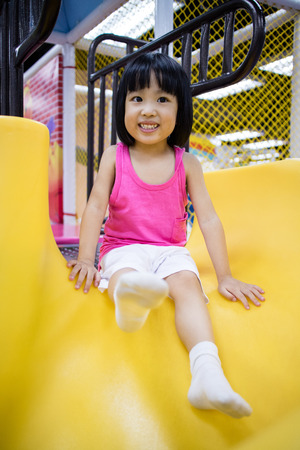 asia children: Asian Chinese Little Girl Playing on the Slide at Indoor Colourful Playground
