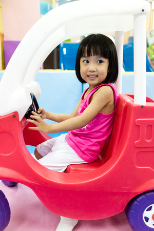 Asian Little Chinese Girl Playing Toy Car in indoor Playground
