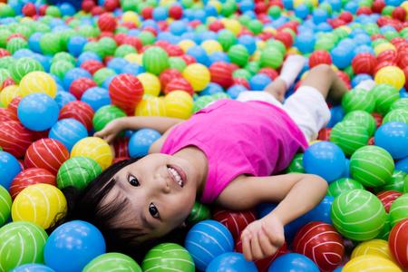 Aziatische Weinig Chinees meisje spelen met kleurrijke plastic ballen in Indoor speeltuin Stockfoto