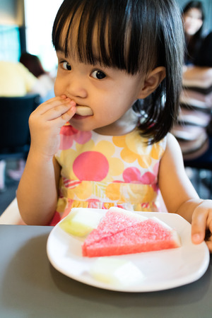 baby sitting: Asian Little Chinese Girl Eating Fruits in a Restaurant Stock Photo