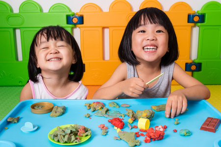 baby toys: Asian Little Chinese Girls Playing with Colorful Clay in Indoor Playground