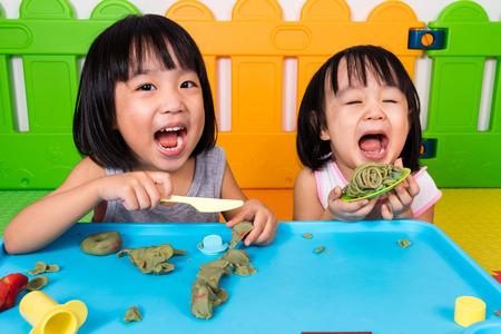 niñas chinas: Asiáticos niñas chinas que juegan con la arcilla de colores en patio interior