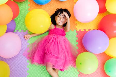 Asian kleine chinesische Mädchen auf dem Boden unter bunten Luftballons in Indoor-Spielplatz-Liegen
