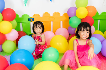 Asian Little Chinese Girls Playing with Colorful Balloons in Indoor Playground
