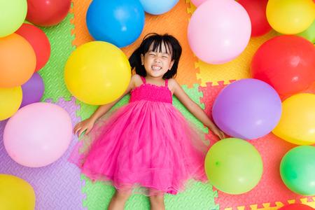 Aziatisch Chinees Meisje liggend op de vloer tussen de kleurrijke ballonnen in Indoor speeltuin