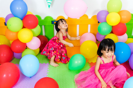 niñas chinas: Asian Little Chinese Girls Playing with Colorful Balloons in Indoor Playground