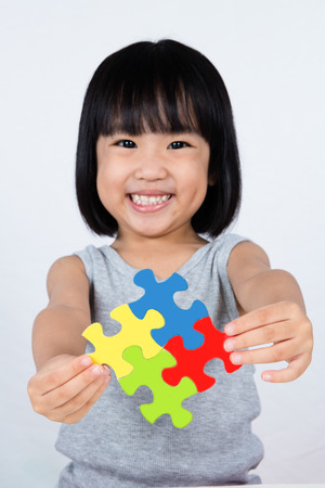 asia children: Asian Little Chinese Girl Playing Colorful Puzzle in isolated White Background