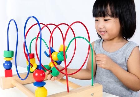 niños felices: Poco Muchacha china asiática que juega el juguete educativo colorido en el fondo blanco aislado