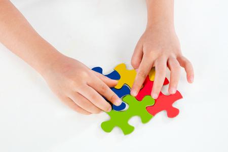 Kind spielen Bunte Puzzle in isolierten weißen Hintergrund
