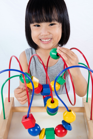 preschooler: Asian Little Chinese Girl Playing Colorful Educational Toy in isolated White Background