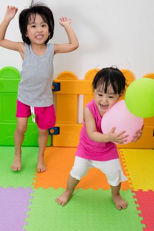 niñas chinas: Asiáticos niñas chinas juegan con los globos en patio interior