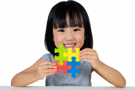 Asian Little Chinese Girl Playing Colorful Puzzle in isolated White Background Stock Photo - 63039705