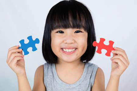 Asian Little Chinese Girl Playing Colorful Puzzle in isolated White Background