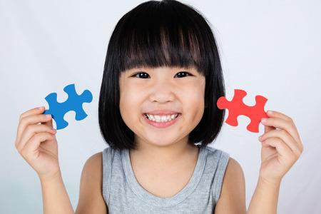 Poco asiático niña china colorido juego de rompecabezas en el fondo blanco aislado