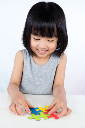 puzzle background: Asian Little Chinese Girl Playing Colorful Puzzle in isolated White Background