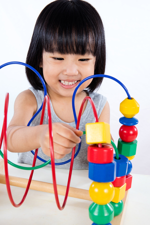 asia children: Asian Little Chinese Girl Playing Colorful Educational Toy in isolated White Background
