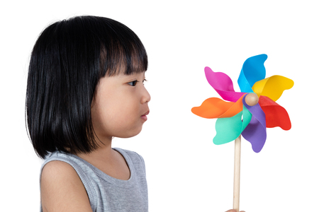 asia children: Asian Little Chinese Girl Playing Colorful Pinwheel in isolated White Background