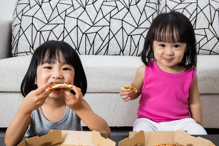 niños comiendo: Asiáticos niñas chinos que comen la pizza en el hogar