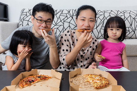 Happy Asian Chinese Family Eating Pizza Together at Home Stock Photo
