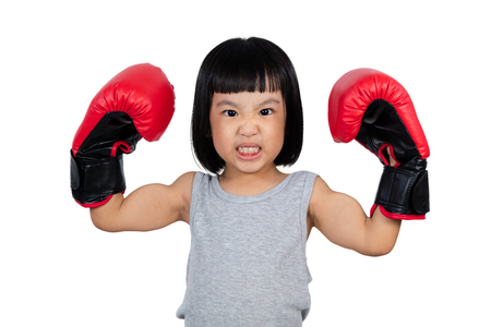 fierce competition: Chinese little girl wearing boxing glove showing power in isolated white background.