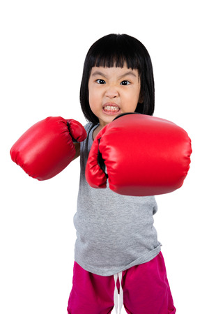 fierce competition: Asian Little Chinese Girl Wearing Boxing Glove With Fierce Expression in isolated white background.