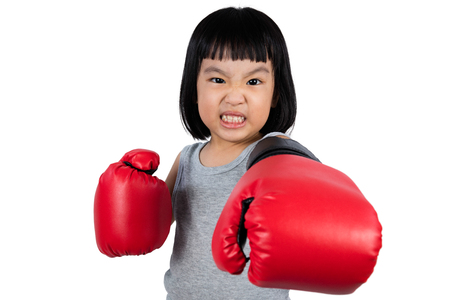 fierce: Asian Little Chinese Girl Wearing Boxing Glove With Fierce Expression in isolated white background.