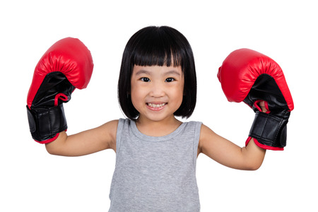 Chinese little girl wearing boxing glove showing power in isolated white background.