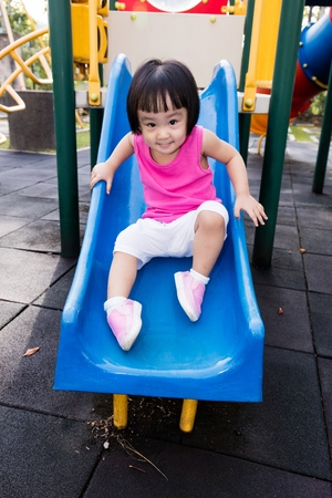 Asian Little Chinese Girl sliding at the playground.